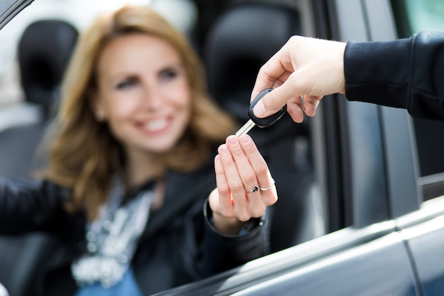 Verkäufer, der die schlüssel zu einem neuen auto überreicht