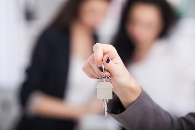 Verkäufer, der ein musterhaus in der hand trägt, liefert dem käufer den hausschlüssel
