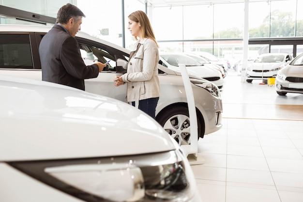 Verkäufer, der einem kunden ein auto am neuwagenausstellungsraum zeigt