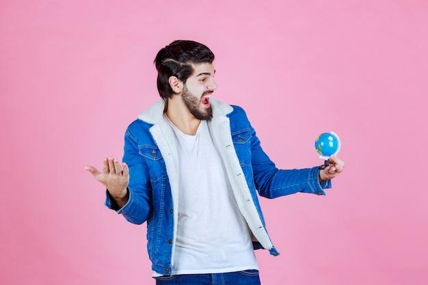 Verkäufer, der einen mini-globus hält und das produkt fördert