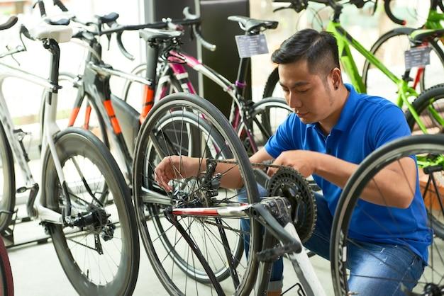 Verkäufer, der fahrradkette einstellt