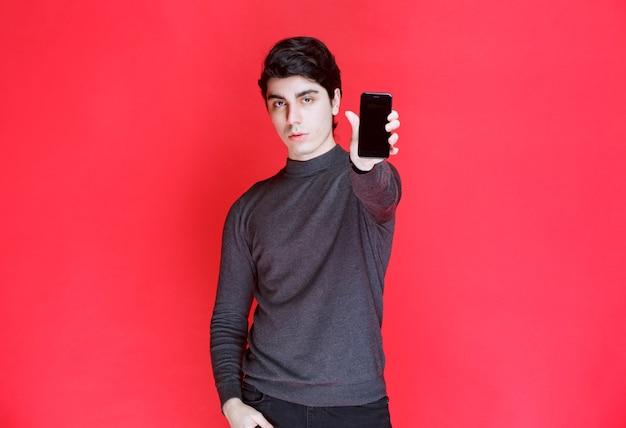 Verkäufer, der funktionen eines neuen smartphones bewirbt und zeigt