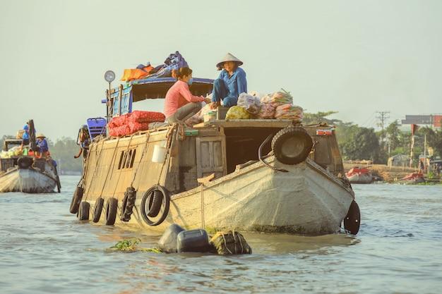 Verkäufer, der gemüse auf sich hin- und herbewegendem markt nga nam im mekong-delta vietnam verkauft.