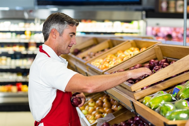 Verkäufer, der gemüsekasten füllt