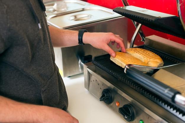Verkäufer, der hotdog in der fast-food-snackbar macht