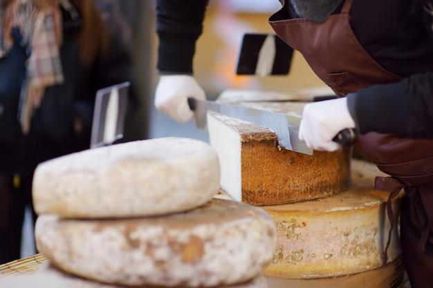 Verkäufer, der organischen käse auf landwirtmarkt in straßburg, frankreich schneidet.