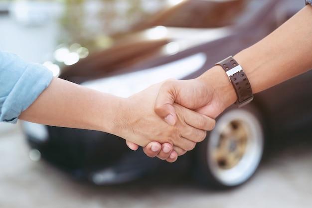 Verkäufer, der schlüssel zum kunden gibt, während händeschütteln im modernen autohaus, nahaufnahme. neues auto kaufen