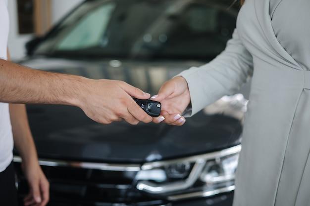 Verkäufer geben der frau schlüssel von neuem. nahaufnahme der hände vor dem auto