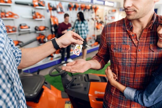 Verkäufer gibt dem jungen mann und dem mädchen die schlüssel.