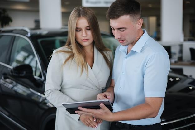 Verkäufer im gespräch mit frau und hilfe bei der auswahl neuer automänner und -frauen im autohaus-mann mit