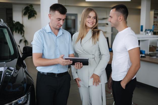 Verkäufer im gespräch mit paaren und hilfe bei der auswahl neuer automänner und -frauen im autohaus-mann mit
