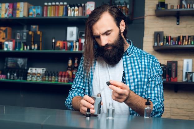Verkäufer im vipeshop zeigt, wie man elektronische zigarette füllt.