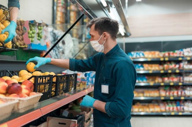 Verkäufer in einer schutzmaske, die mit obst vor der theke steht. coronavirus in der stadt