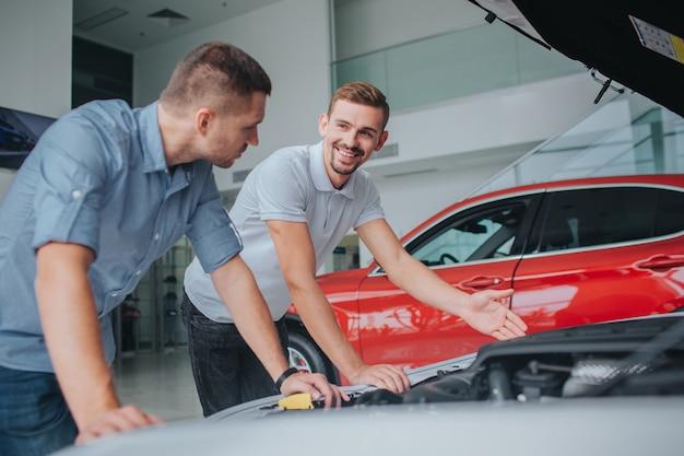 Verkäufer in weißem sirt steht an geöffneter karosserie und zeigt darauf. er sieht einen mann an und lächelt. mann im grauen hemd stützt sich auf auto und schaut verkäufer an. er wählt auto.