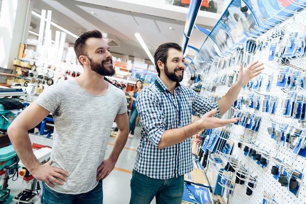 Verkäufer ist zeigt dem kunden die auswahl der ausrüstung