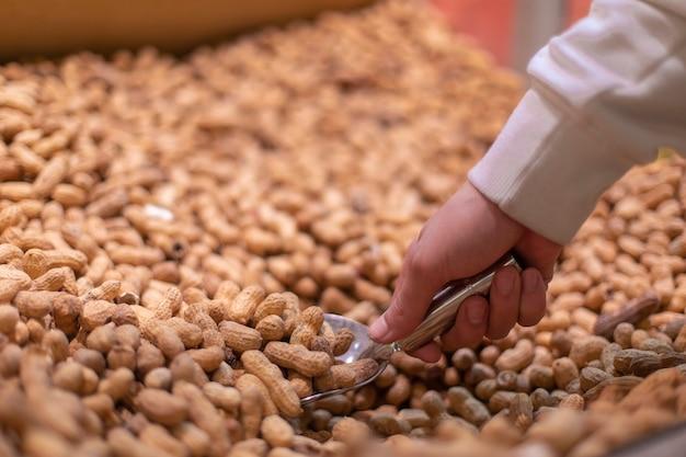 Verkäufer nimmt erdnüsse in schalen auf dem markt. hochwertiges foto
