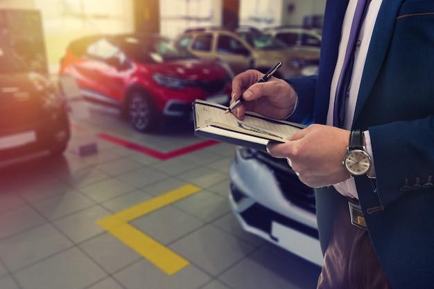 Verkäufer schreiben auf notizblock über den verkauf oder die autovermietung