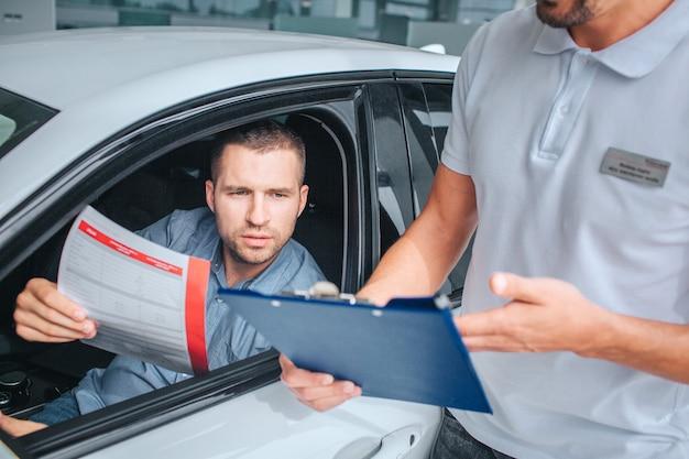 Verkäufer steht am weißen auto und hält tablette in händen. er zeigt darauf. ein anderer mann sitzt im auto und hält versicherungspapier. er ist ernst und konzentriert. sie haben ein gespräch.
