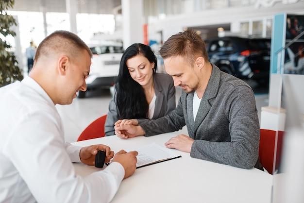 Verkäufer und ein paar machen den verkauf eines neuen autos im ausstellungsraum aus.