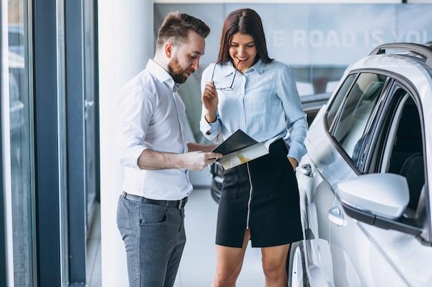 Verkäufer und frau, die nach einem auto in einem autosalon suchen