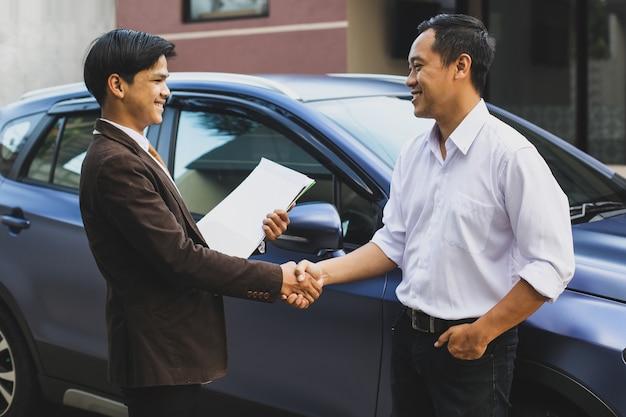 Verkäufer und kunde, die ein auto beim händeschütteln gekauft haben