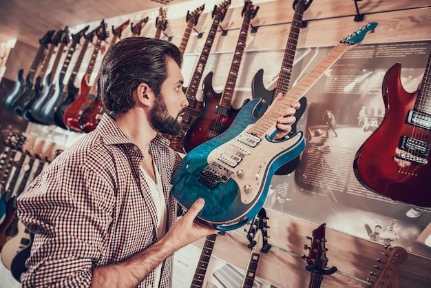 Verkäufer von instrumenten setzt elegante e-gitarre auf regal