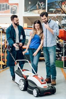 Verkäufer zeigt kunden neuen rasenmäher