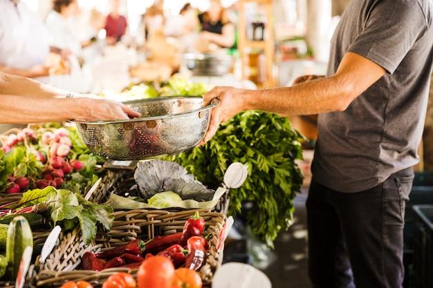 Verkäuferhand, die edelstahlbehälter während kaufendes gemüse des kunden am markt hält