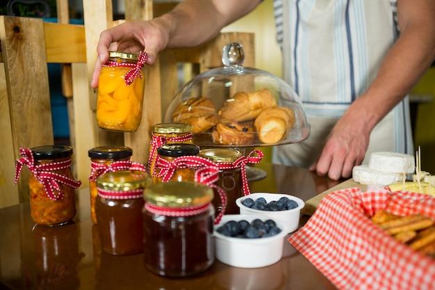 Verkäuferin arrangiert marmelade und einmachgläser