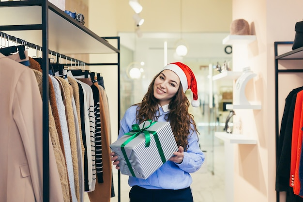 Verkäuferin bietet einem bekleidungsgeschäft in weihnachtskleidung ein weihnachtsgeschenk an