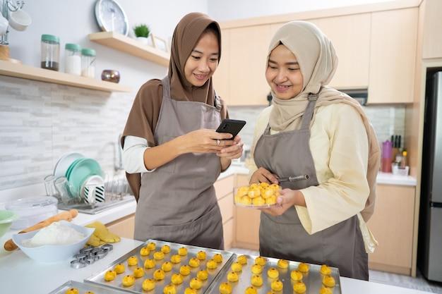 Verkäuferin der muslimischen frau zu hause, die produkt des nastar-kuchens macht