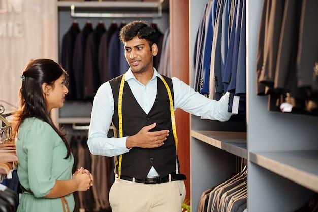 Verkäuferin, die eine auswahl an jacken und männlichen anzügen für junge frauen im laden zeigt
