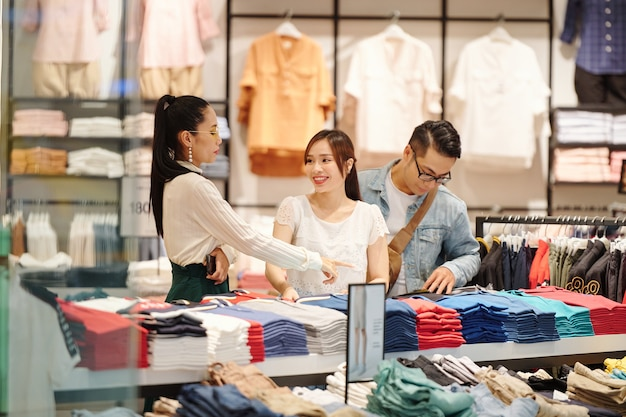 Verkäuferin hilft jungen paaren bei der auswahl von kleidung im kaufhaus