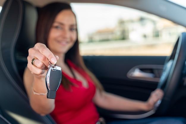 Verkäuferin im auto übergibt dem kunden den schlüssel für eine probefahrt