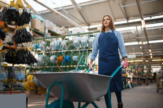 Verkäuferin in schürze hält gartenwagen im laden für gärtner. frau verkauft ausrüstung im laden für blumenzucht, floristeninstrumentenverkauf