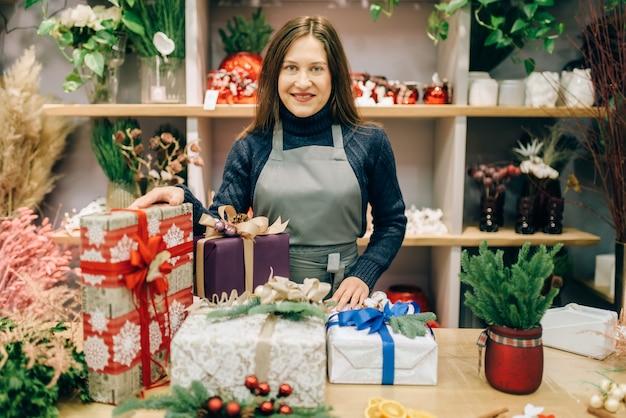 Verkäuferin mit geschenkboxen in festlichem geschenkpapier mit bändern, handgemachte dekoration. präsentiert verpackungsservice, diy dekor