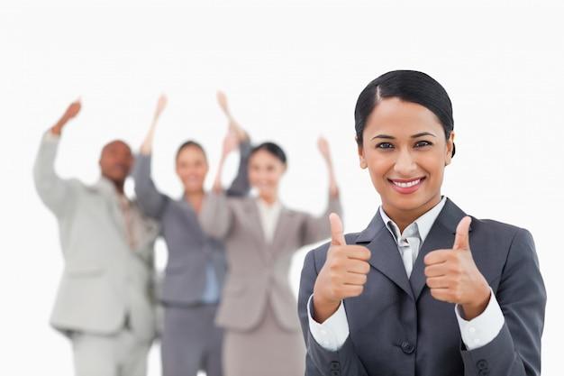 Verkäuferin mit jubelndem team hinter ihr zustimmung gebend