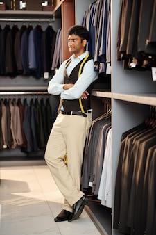 Verkäuferin mit maßband, die herrenanzüge, jacken und hosen im geschäft verkauft