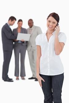Verkäuferin mit mitarbeitern hinter ihr am telefon