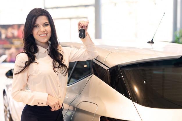 Verkäuferin mit schlüssel präsentieren ein neues auto im autohaus