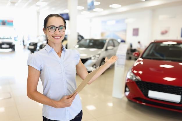 Verkäuferin mit zwischenablage in der hand, die ein neues auto im günstigen kredit des autohauses zeigt