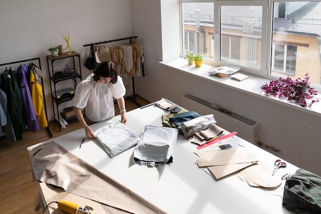 Verkäuferin packt kleidung ein, um sie an den kunden im studio-atelier zu senden