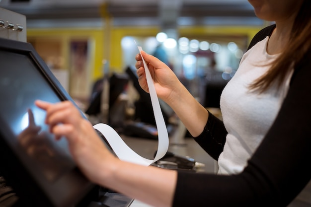 Verkäuferin / shopgirl druckt eine quittung / rechnung für einen kunden, verkaufszeit, rabattzeitraum