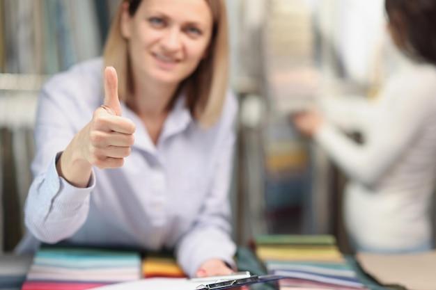 Verkäuferin zeigt daumen nach vorne mit stoffproben im laden, nahaufnahme von hoher qualität