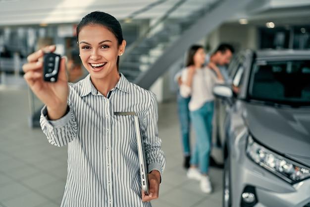 Verkäuferin zeigt die autoschlüssel zur kamera. geschäftskonzept, autoversicherung, auto verkaufen und kaufen, autofinanzierung, autoschlüssel für fahrzeugverkaufsvertrag.