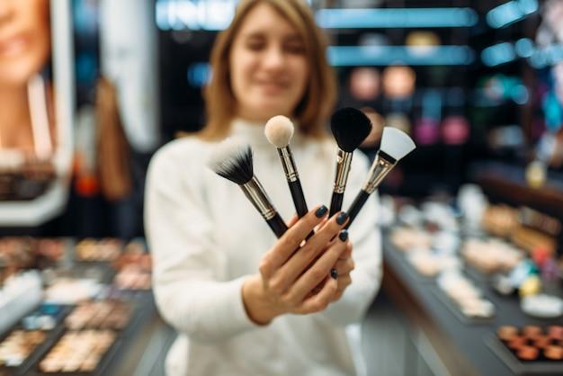 Verkäuferin zeigt pinsel im make-up-shop. kosmetikauswahl im schönheitssalon, make-up