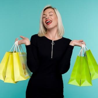 Verkauf junge lächelnde frau, die einkaufstaschen im schwarzen freitag-feiertags-glückliches mädchen auf blauem hintergrund hält