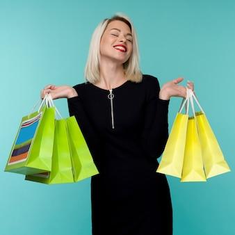 Verkauf. junge lächelnde frau, die einkaufstaschen im schwarzen freitagurlaub hält. glückliches mädchen auf blau