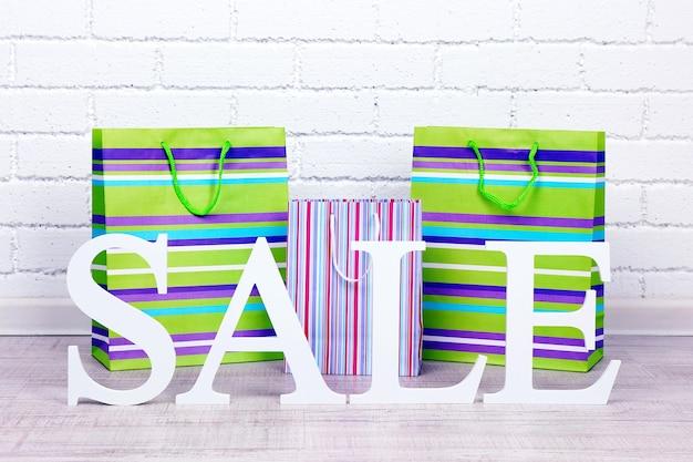 Verkauf mit taschen auf dem boden auf hellem hintergrund