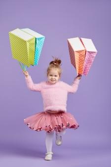 Verkauf von kinderprodukten. porträt des lustigen kleinen kindermädchens auf lila raum, der einkaufstaschen, paket hält. blick in die kamera. banner. platz für text.